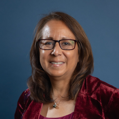 Academic headshot; A Latin American woman with shoulder-length, brown hair, smiles at the camera. She is wearing black, rectangular glasses, a necklace with a black ball pendant, a red blouse, and a red velvet blazer