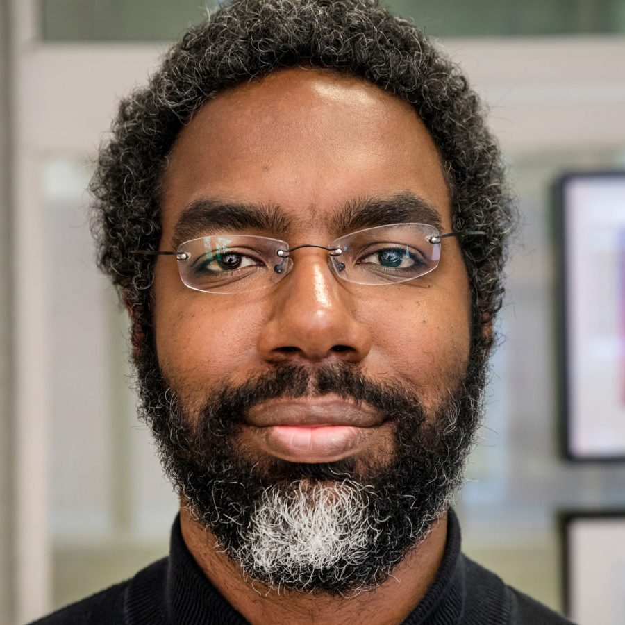 Headshot; A Black man with short, tightly curled hair that connects to a full beard with a gray patch in the center; staring at the camera with a neutral expression. He is wearing small, rectangular glasses with no frame, and a black, mock neck sweater