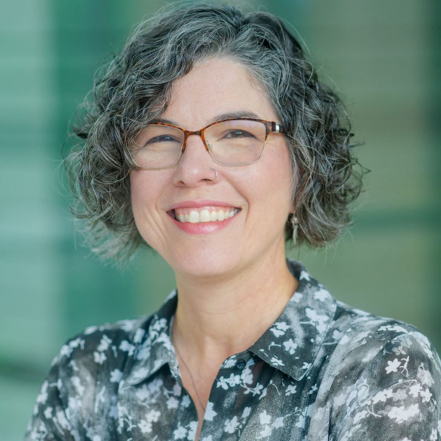 Academic headshot; A latin american woman with black and gray, curly hair that just covers the ears, smiles at the camera. She is wearing square classes with exposed frames and a black and white, floral, dress shirt
