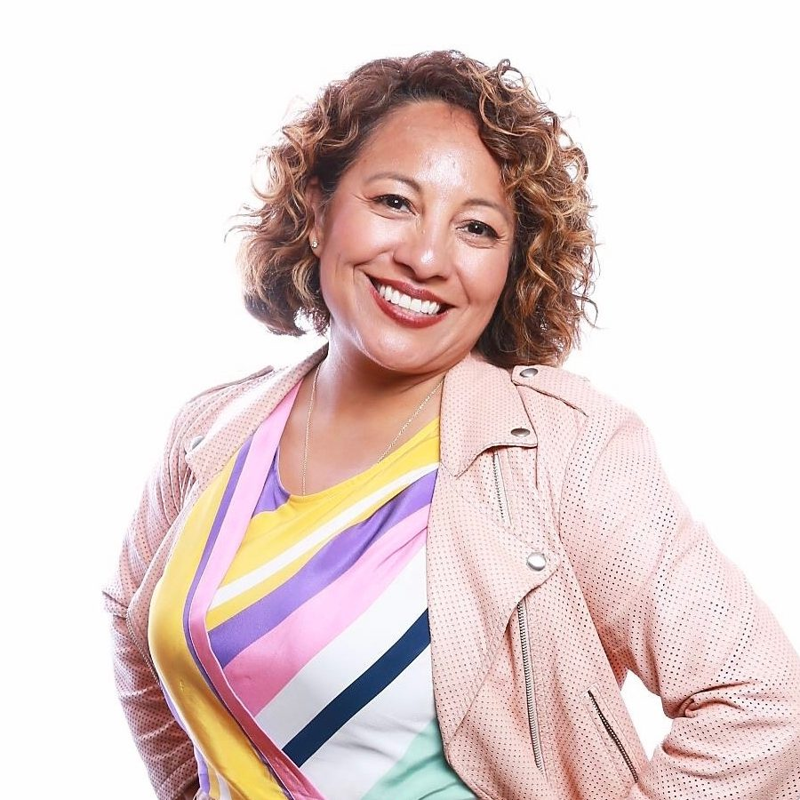 headshot; A latin american woman with chin-length, curly, light brown hair, smiles directly at the camera. She is wearing dark red lipstick, a silver chain necklace, a dress with white, yellow, pink, purple, and navy blue stripes, and a light pink jacket