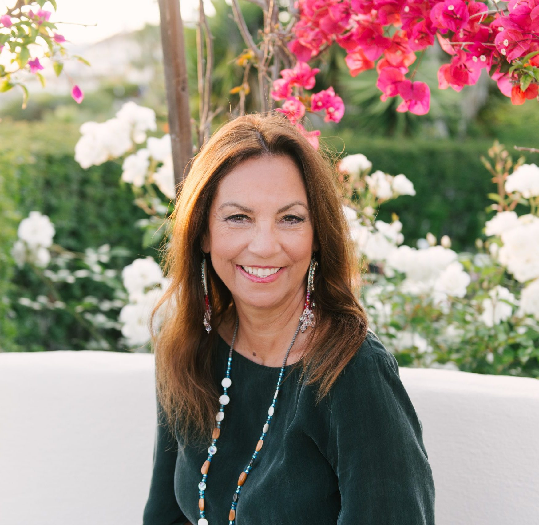 A Native-American woman with armpit length, light brown hair, smiles directly at the camera. She is wearing a dark green long sleeve shirt, a blue, white and orange beaded necklace and green, red, purple and pink pendant earrings. She is sitting on a white bench in front of a tree with pink and white flowers and some bushes.