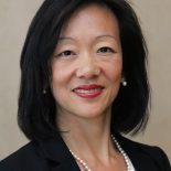 An Asian American Woman with shoulder length, black, straight hair stares directly at the camera, smiling. She is wearing a red lipstick, pearl earrings, a pearl necklace and a white and red blouse with a black blazer over it.