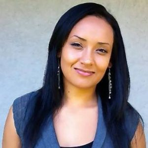 Headshot of a Latin American woman with a closed mouth smile, staring at the camera. She has chest-length, straight, black hair. She is wearing a dark blue vest over a black tank top.
