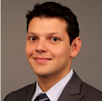 A Latino man with dark brown hair looks directly at the camera with a closed mouth smile. He is seen from the chest up wearing a gray suit, white collared shirt, and navy blue and white pinstripe tie.