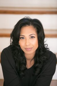 An African American woman with chest length, black, curled hair looks directly at the camera. She is wearing a black, long sleeve blouse