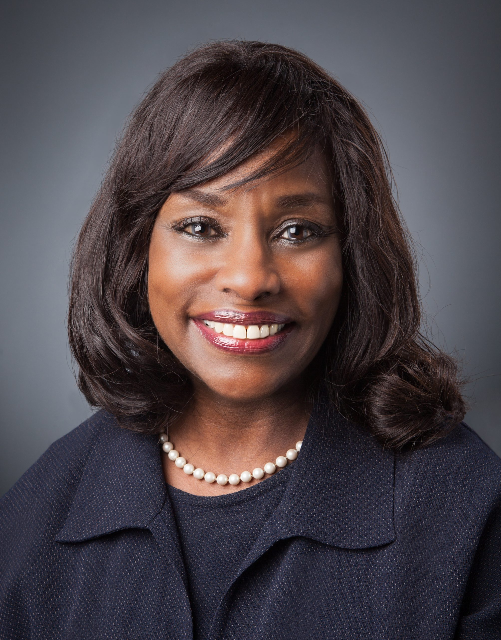 An African-American woman with shoulder-length dark brown hair smiles directly at the camera, close-up. She is wearing dark red lipstick, a pearl necklace and a black blazer with a matching black shirt under it. The background is light grey.