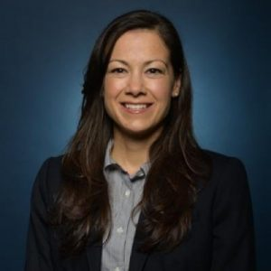 Academic headshot; a latin american woman with chest-length, straight, dark brown hair, smiles directly at the camera. She is wear a gray-blue button-up shirt with a black blazer.
