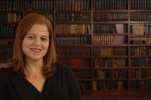 A fair-skinned, Latin American woman with light brown hair smiles at the camera. She is wearing red lipstick, a black v-neck blouse and silver necklace. She is seen from the chest up on the left side, in front of a brown bookcase.