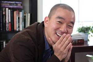 An Asian man stares directly at the camera smiling, his hands are resting on his chin. He has black hair in a buzz cut and is wearing a blue collared dress shirt with a brown blazer. Behind him is a full bookcase and a table with a plant on it.