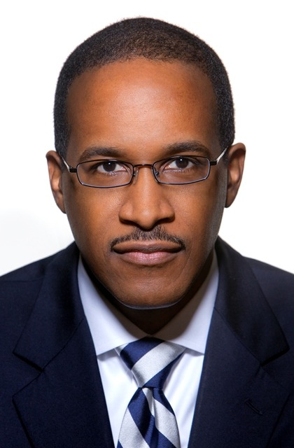 An African American man with a buzz cut, black hair, and glasses stares directly at the camera with a neutral expression. He is seen from chest up, wearing a navy blue suit over a white, collared shirt and blue and white diagonally striped tie.