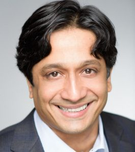 Headshot of an Indian man smiling directly at the camera. He has short, straight, black hair. He is wearing a white collared shirt and gray and blue plaid suit jacket.
