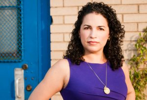 Headshot; A latina woman with shoulder length, dark brown, curly hair, stares directly at the camera with a neutral expression. She is wearing a purple sleeveless dress with a gold, round, pendant necklace.