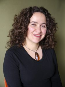 Headshot of a Latin American woman with curly, light brown, shoulder length hair smiles at the camera. She is wearing a brown, teardrop-shaped pendant necklace and a black longsleeve shirt.