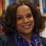 Headshot of a latin american woman with chin length, brown hair smiling directly at the camera. She is wearing a dark gray blazer and a blue and beige scarf.