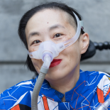 An Asian American woman in a power chair. She is wearing a blue shirt with a geometric pattern with orange, black, white, and yellow lines and cubes. She is wearing a mask over her nose attached to a gray tube and bright red lip color. She is smiling at the camera. Photo credit: Eddie Hernandez Photography