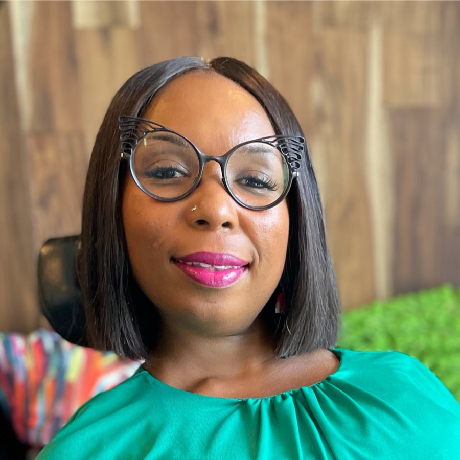 Smiling African-American woman wearing black cat-eye glasses with a butterfly wing detail. She is wearing a green blouse and hot pink lipstick. Her hair is chin length and straight. Although not depicted, she's a power wheelchair user.