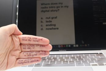 A hand with a formula written on it is in the foreground in front of a laptop with a test question, implying that the test taker is referencing her hand to get the right answer.