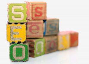 A pile of vintage alphabet building blocks spell S-E-O.