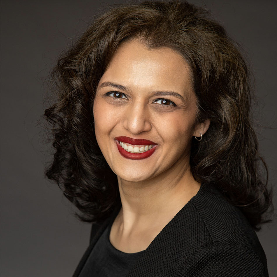 A Pakistani woman with curly, dark brown hair smiles directly at the camera. She is seen from the chest up, wearing a black shirt and black blazer.
