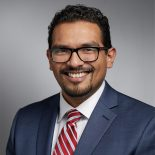 A Mexican man with short, curly, dark brown hair and a short beard smiles directly at the camera. He is wearing square, black, glasses, a while collared shirt, light blue suit jacket, and red, white, and blue pinstripe tie.