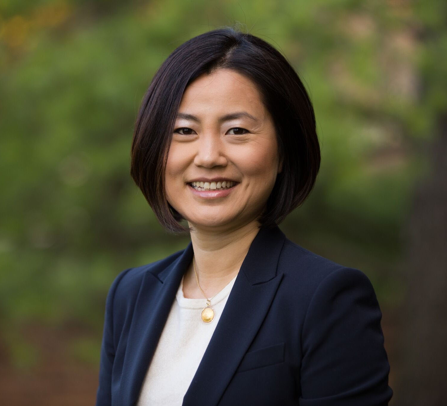 An Asian woman with straight, chin length, dark brown hair, smiles directly at the camera. She is wearing a white scoop neck shirt, navy blue blazer, and a gold pendant necklace.