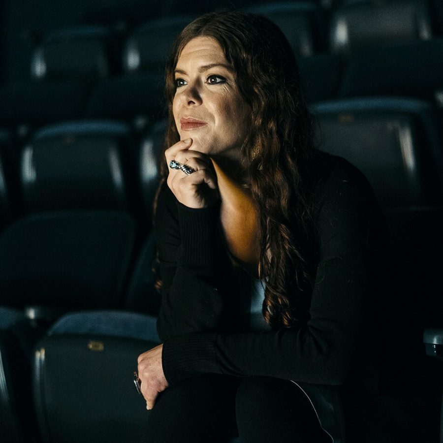 A Cherokee woman with wavy, chest length, dark brown hair sits in a chair of a dark theatre, staring off into the distance, chin resting on her hand. She is wearing black tights, a light blue dress, a black cardigan, and thick silver rings.