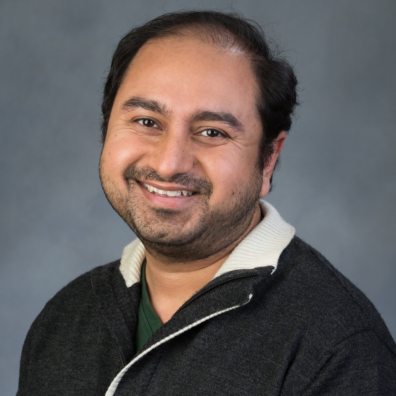 Academic headshot; An Indian man with short, ear length, straight, black hair, smiles directly at the camera. He is wearing a dark green shirt and a black, zip-up sweater with a white collar