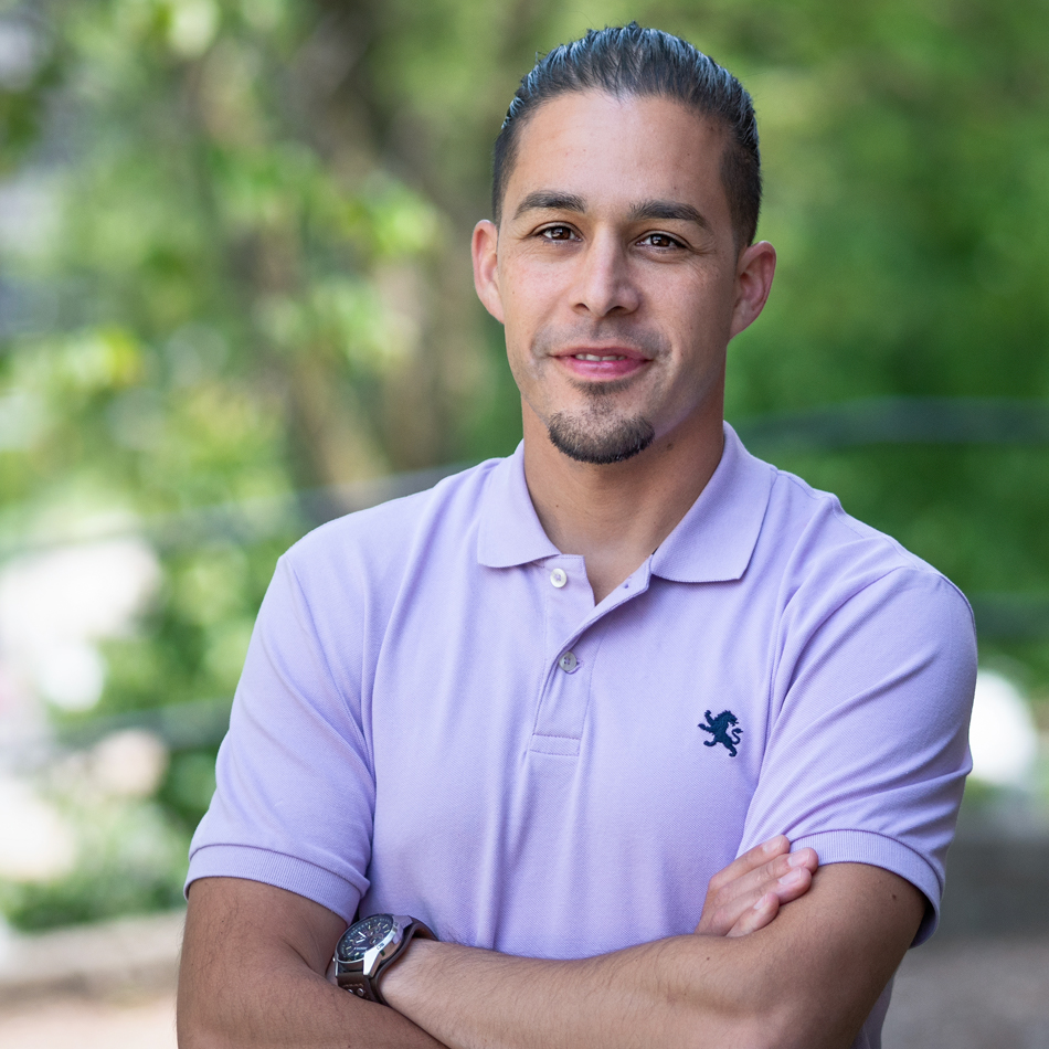 A Latino man with short, straight, black hair with buzzed sides, stares directly at the camera with a small smile. He has a goatee and is wearing a lavender polo shirt and watch.